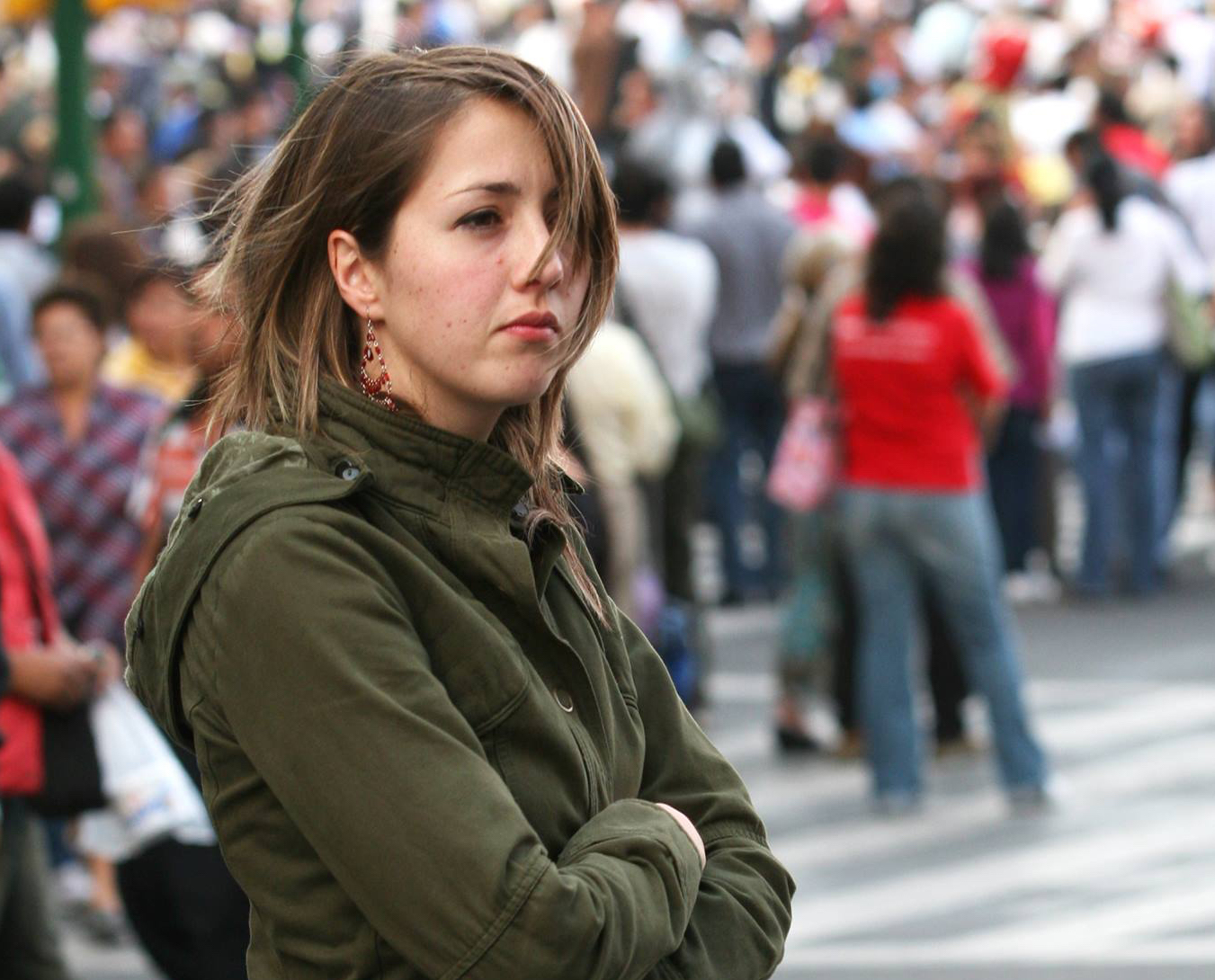 Ana Emilia Felker with brown hair covering half her face wearing an army green jacket with arms folded looking out into a crowd.