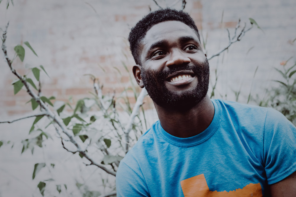 Nigerian American poet Ayokunle Falomo in a light blue t-shirt with short hair and a beard smiles and looks up.