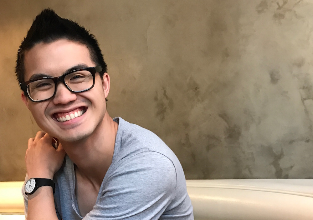 Joshua Nguyen smiles at the camera wearing a gray t-shirt and dark rimmed glasses with short dark hair.
