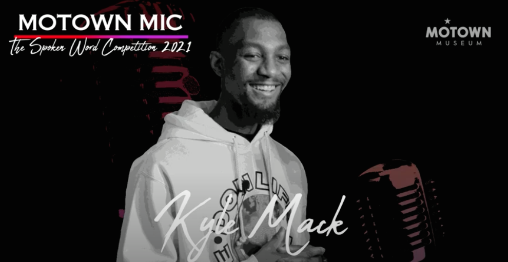 Black and white screenshot of Kyle Mack in front of the mic for Motown Spoken Word competition.