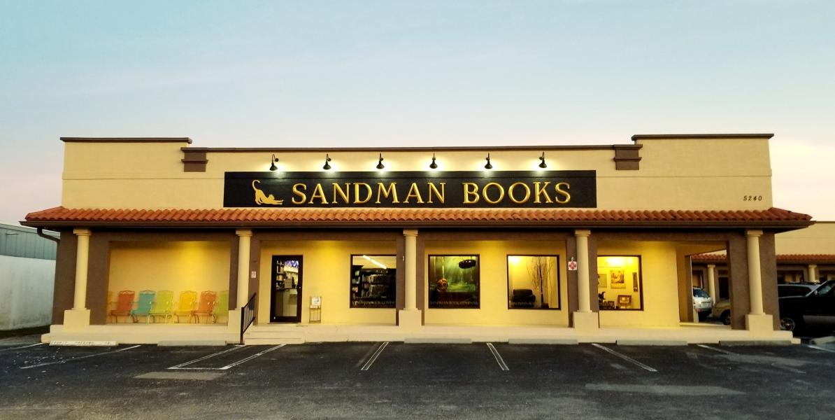 Storefront with four windows and one glass door, lights aiming on the black sign with gold letters for Sandman Books