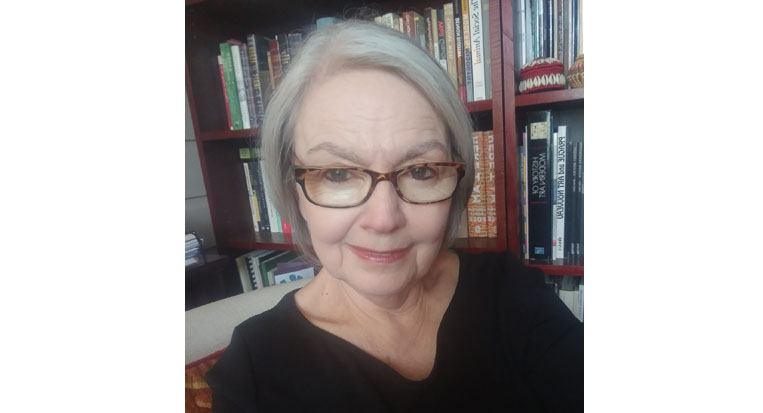 Robin Davidson sits in front of a bookshelf in a black top with glasses and short gray hair.