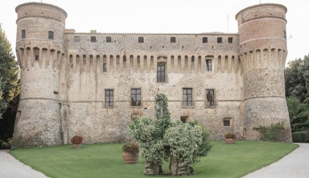 Civitella Ranieri castle, a 15th-century stone building with two round turrets surrounded by green lawn