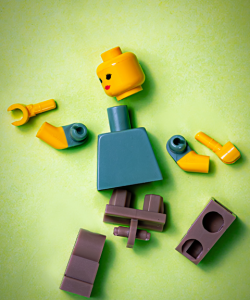 A deconstructed lego person is spread out on a light green surface.