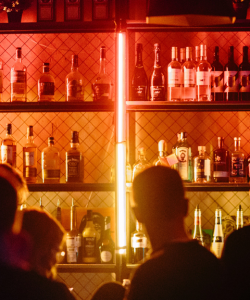 The wall behind a bar is illuminated by a red-and-yellow neon light. Bottles of liquor and wine are perched on shelving units. Several out-of-focus figures are standing in front of the bar.
