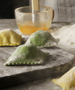 Flour plump homemade ravioli sit on the kitchen table. They are lightly dusted with flour, waiting to be cooked. Toward the back is a small glass bowl with an egg mixture and a mound of white flour.