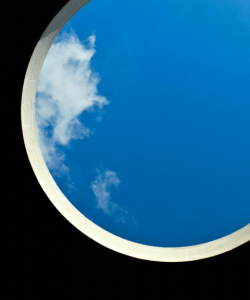 A view of the sky through a large circular opening; wisps of cloud drift at the left edge of the frame.