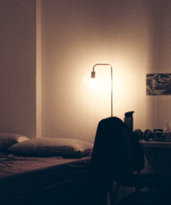 Film photo of a bedroom. A floor lamp illuminates striped pillows on a bedspread, while the rest of the room remains mostly dark.
