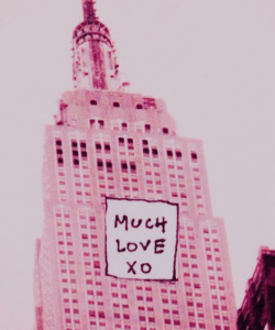 """Edited photo of the upper half of the Empire State Building. Everything is in pink tones. A small white square with the handwritten words """"MUCH LOVE XO"""" is pasted on top of the photo, on the face of the building."""