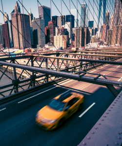 A solitary yellow taxicab crosses over the Brooklyn Bridge on a clear, bright day. Skyscrapers in downtown Manhattan are visible in the background.