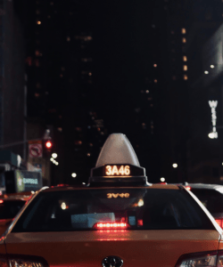 At night in New York City, the backside of a yellow taxicab is illuminated by headlights.