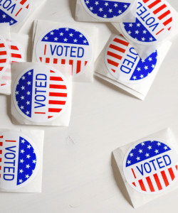 """A dozen or so """"I VOTED"""" stickers with an American flag design are spread out on a white table."""