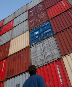 A person with their back to the camera gazes up at a stack of large shipping containers