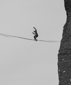 A person, arms raised, balances on a tightrope far above the ground in Smith Rock State Park in Oregon.