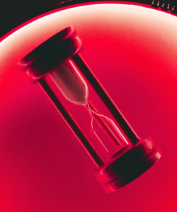 An hourglass sand timer is illuminated by red light.