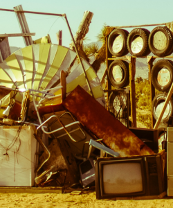 Discarded household items—including a CRT TV, tires, chairs, a mini-fridge, and other detritus—are piled up in the desert. Everything is cast in warm, late-afternoon light.
