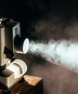A vintage Dukane film projector shines a beam of light through a dark room