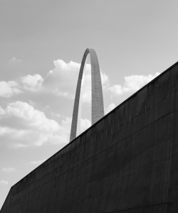 A view of the Gateway Arch in St. Louis. The top half of the stainless steel monument is visible, while the bottom half is obscured by a large wall.