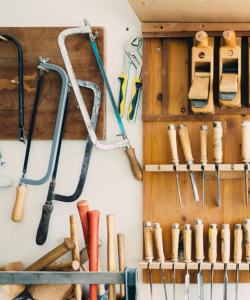 Inside a woodworker's studio, saws, files, mallets, and hammers are stored in various wall units.