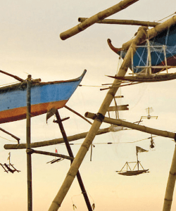 Close-up of the cover of Patrick Rosal's The Last Thing. Toy-sized wooden boats hang suspended from scaffolding that holds larger wooden boats. The sky in the background is a soft yellow.