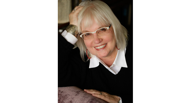 Susan Larson with white-framed glasses and light shoulder length hair smiling and leaning on her arm wearing a black sweater over a white collared shirt.