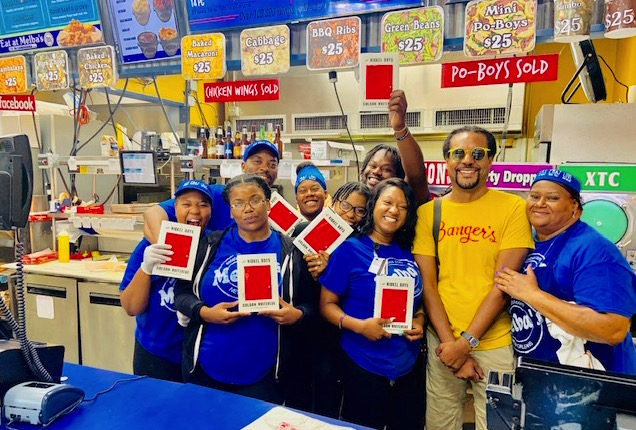 Colson Whitehead in a bright yellow t-shirt with staff at Melba's holding his book and smiling.